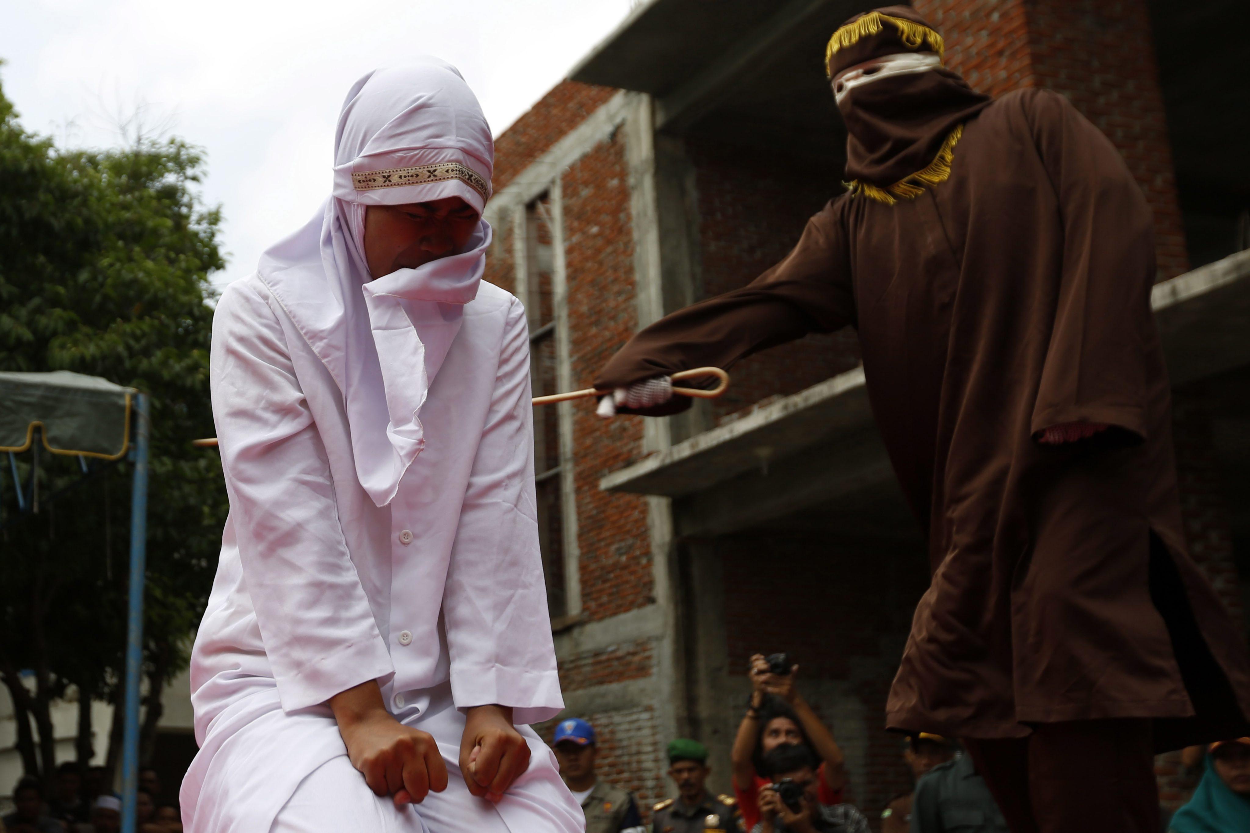 Imaginile agoniei cu o tanara din Indonezia biciuita pentru ca si-a inselat sotul. Femeia, scoasa pe targa din multime