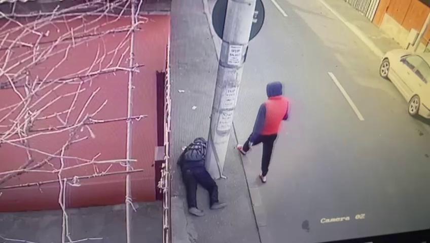 VIDEO. Momentul în care un bărbat care zace inconștient pe stradă este jefuit de un tânăr, în București