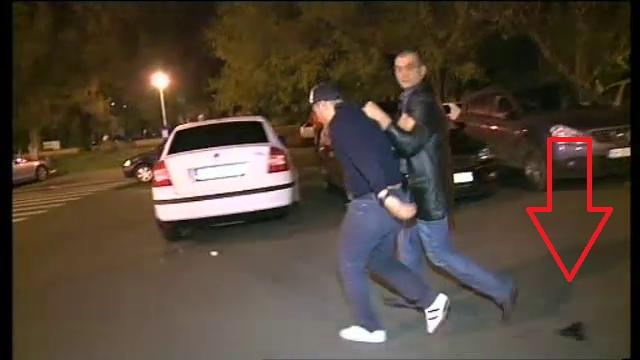 Momentul in care un agent isi pierde pistolul in timp ce baga un suporter in masina de politie