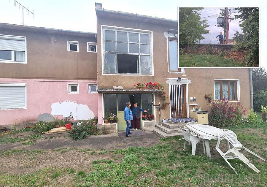 Locatarii unui bloc urcă pe o scară în casă, pentru că nu pot călca pe terenul pe care se află construcția
