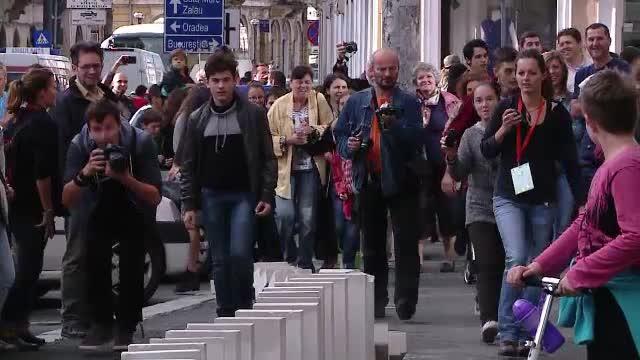 3000 de piese de domino s-au intins pe 1,2 kilometri, in centrul Clujului. Sute de oameni au alergat dupa piesele in cadere