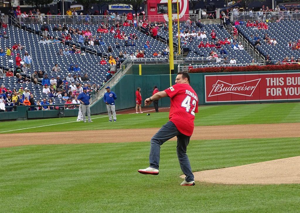 George Maior, chemat să dea lovitura de start la un meci de baseball în SUA. Drapelul României, prezent pe stadion