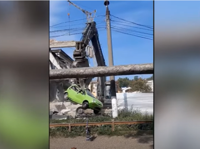 VIDEO Mașină ridicată de un excavator și aruncată peste gard, pe un șantier din Chișinău